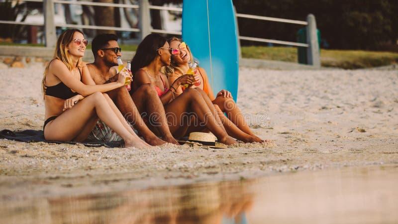 Amici su una festa che spendono tempo alla spiaggia immagini stock libere da diritti