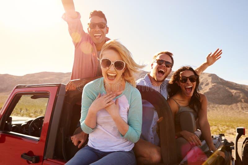 Amici sul viaggio stradale che sta in automobile convertibile fotografie stock