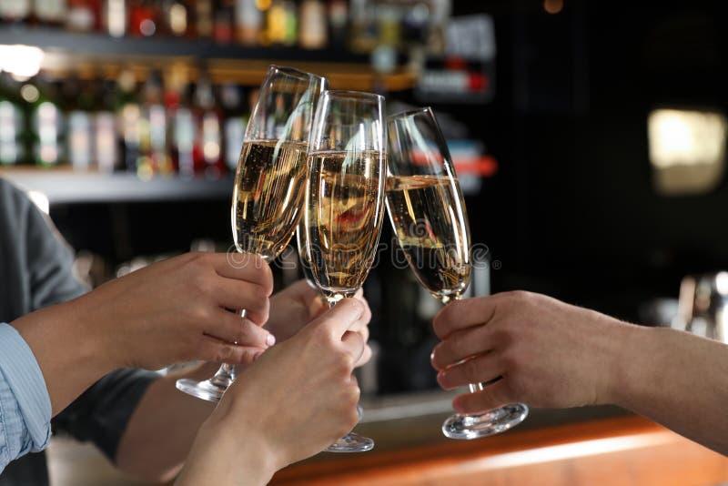 Amici tintinnanti con i vetri di champagne nella barra fotografia stock