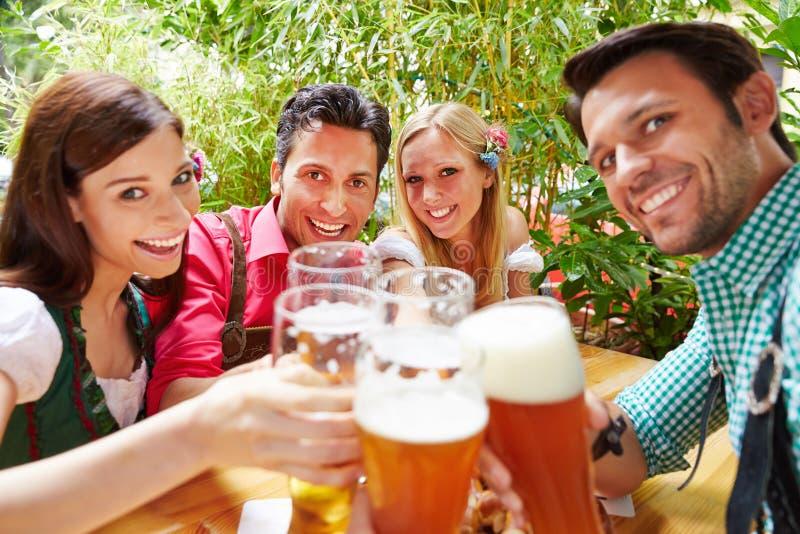 Amici in tintinnio del giardino della birra fotografia stock libera da diritti