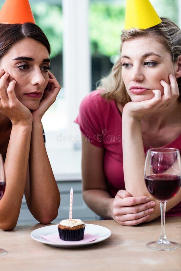 Amici tristi che si siedono alla tavola durante la festa di compleanno immagini stock