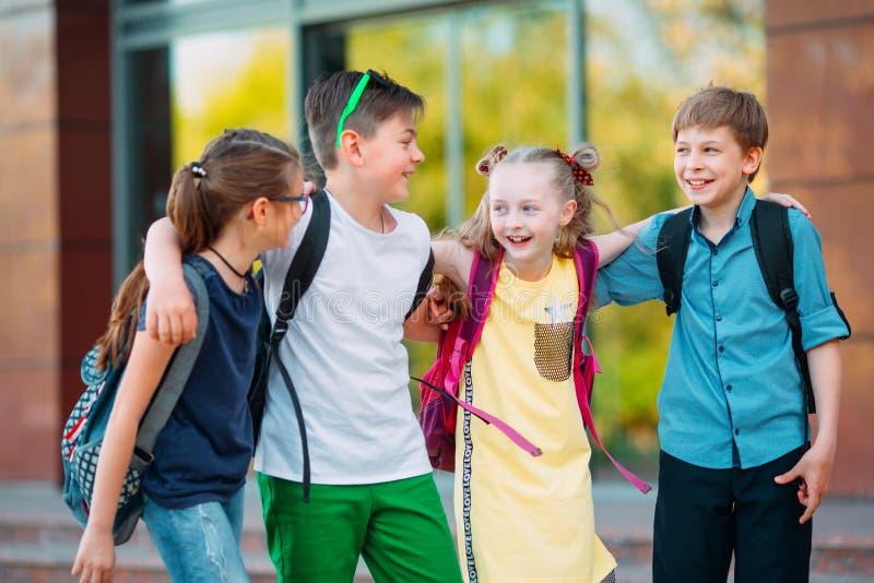 Amicizia del ` s dei bambini Quattro piccoli studenti della scuola, due ragazzi e due ragazze, supporto in un abbraccio sul corti fotografie stock