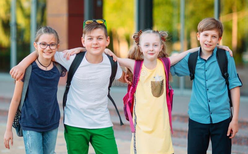Amicizia del ` s dei bambini Quattro piccoli studenti della scuola, due ragazzi e due ragazze, supporto in un abbraccio sul corti fotografia stock libera da diritti