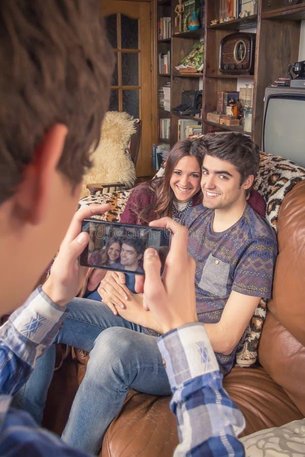 Amico che prende le foto alle coppie adolescenti su un sofà immagini stock libere da diritti