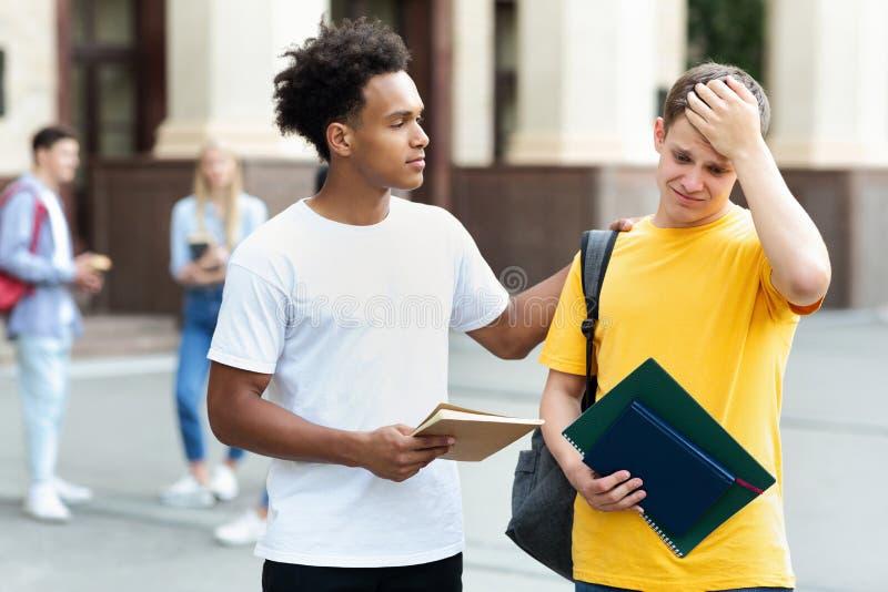 Amico di consolazione del tipo adolescente sopra il cattivo risultato dell'esame fotografie stock libere da diritti