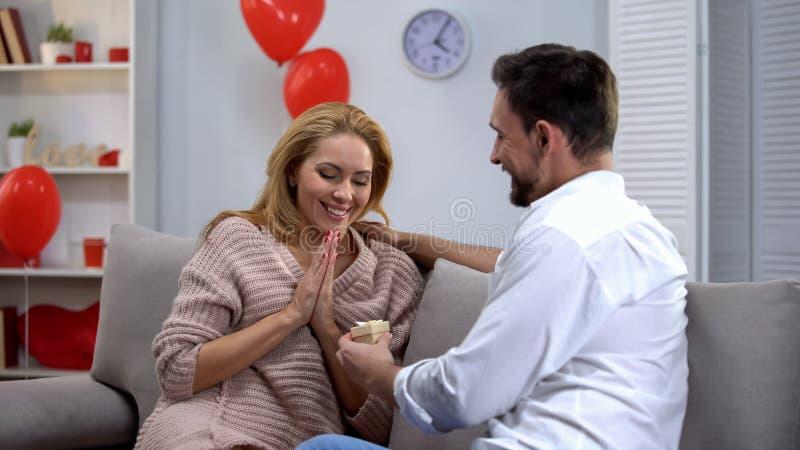 Amie étonnée donnante masculine peu de boîte-cadeau de bijoux au jour de valentines de St image stock
