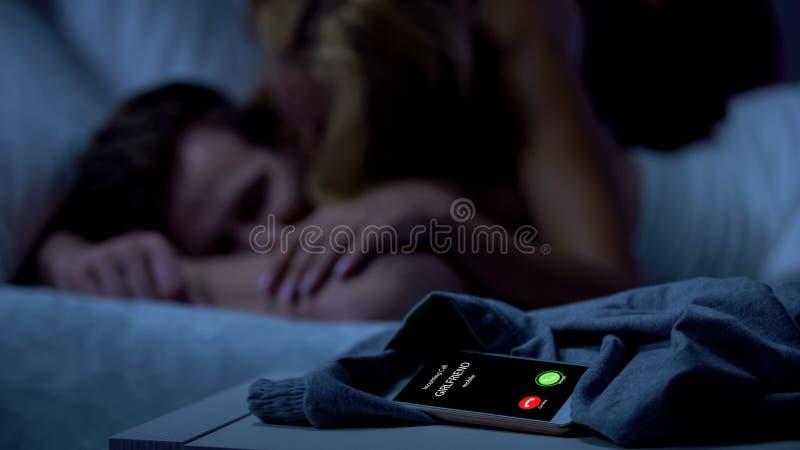 Amie appelant tandis que maîtresse venant et embrassant le mâle somnolent, trahison photo stock