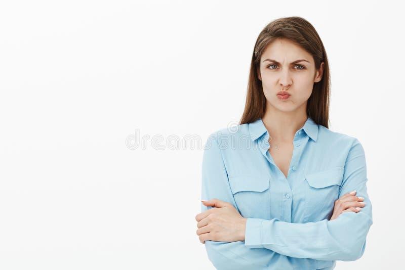 Amie attirante intense sombre dans le chemisier bleu, jugeant des mains lèvres croisées et se pliantes, boudant et fronçant les s images stock