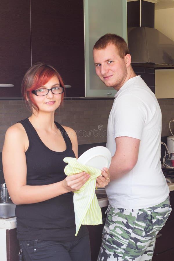 Amie de aide de jeune homme pour faire des plats photos stock