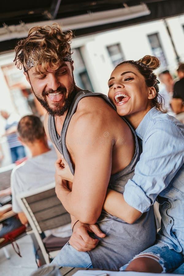 Amie de sourire étreignant l'ami par derrière dans un café photos libres de droits