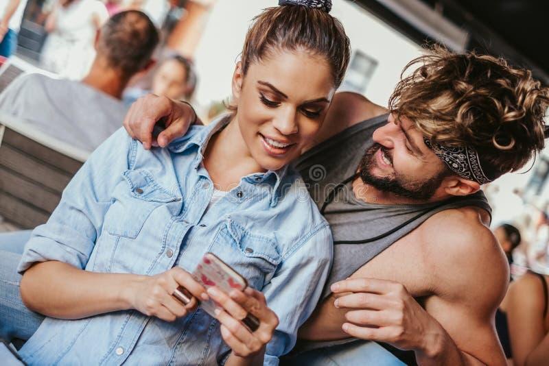 Amie de sourire montrant le téléphone portable à son ami images libres de droits