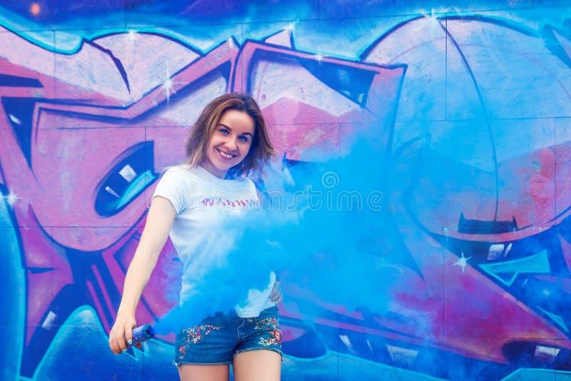 Amie folle et ennuyeuse dans le T-shirt blanc et jeanse court avec une bombe fumigène photographie stock