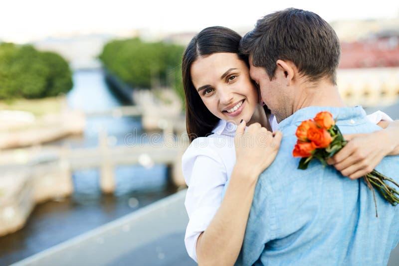 Amie heureuse avec le bouquet caressant son homme image libre de droits
