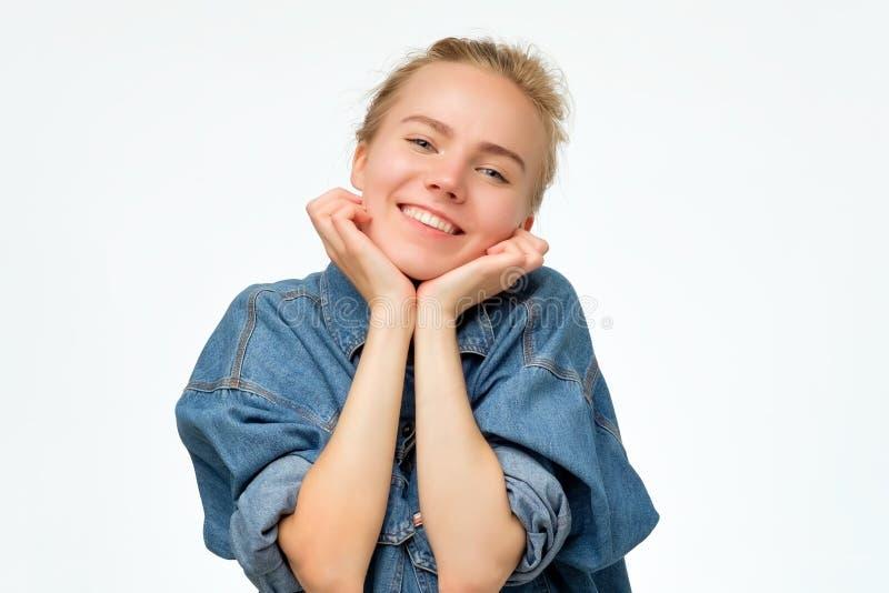 Amie mignonne avec les cheveux blonds souriant largement et le visage de penchement sur des poings photos libres de droits