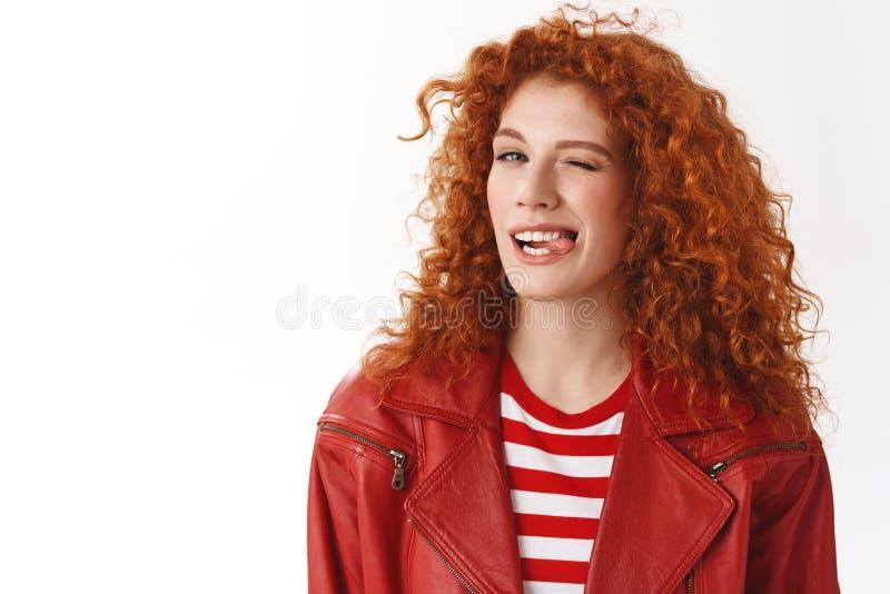 Amie millénaire bouclée rousse élégante impertinente clignant de l'oeil l'humeur positive chanceuse exprès de sourire de langue e image libre de droits