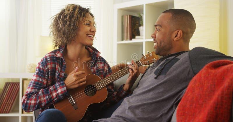 Amie noire mignonne chantant une sérénade à son ami avec l'ukulélé photo stock