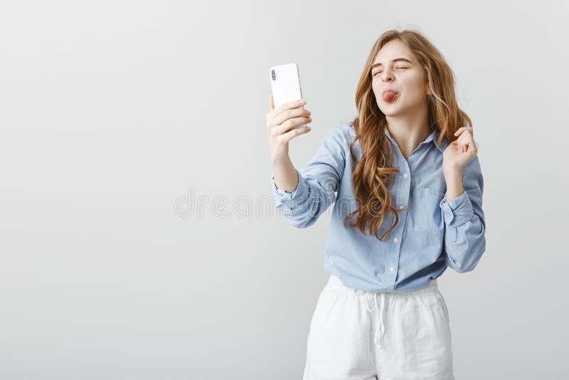 Amie puérile parlant avec l'amant par l'intermédiaire de l'Internet Femme européenne attirante insouciante, tenant le smartphone, photos libres de droits