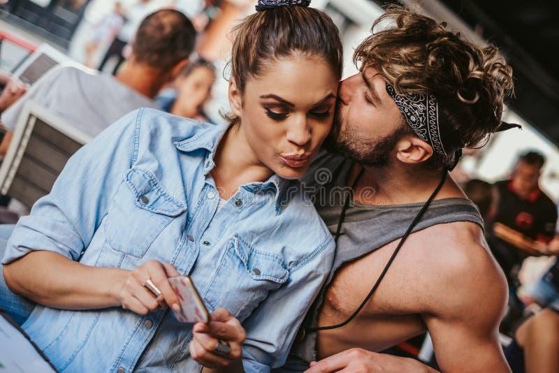 Amie regardant le téléphone portable tandis que l'ami est embrassant lui images libres de droits