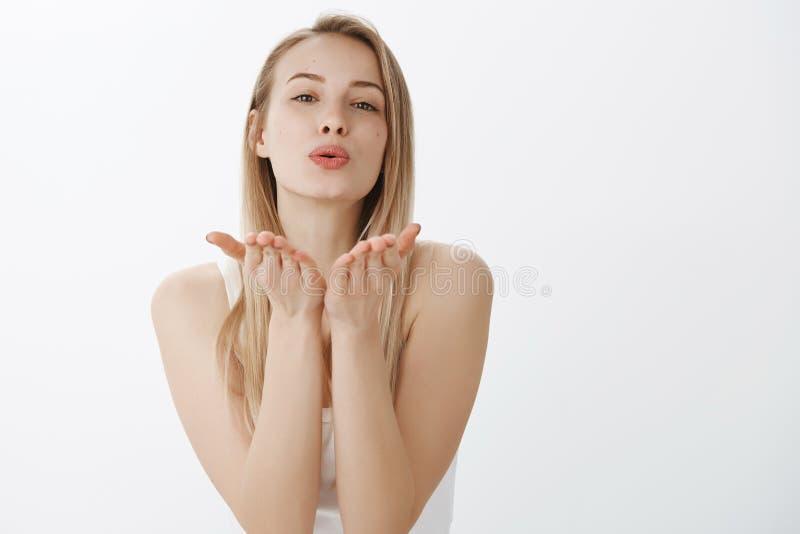 Amie tendre belle passionnée et affectueuse avec les cheveux blonds inclinant en avant en tant que lèvres se pliantes et soulevan photographie stock