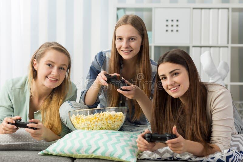 Amies décontractées jouant un jeu vidéo image libre de droits