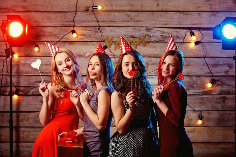 Amies d'ado de fête d'anniversaire Jeunes filles dans les chapeaux et les appui verticaux image stock