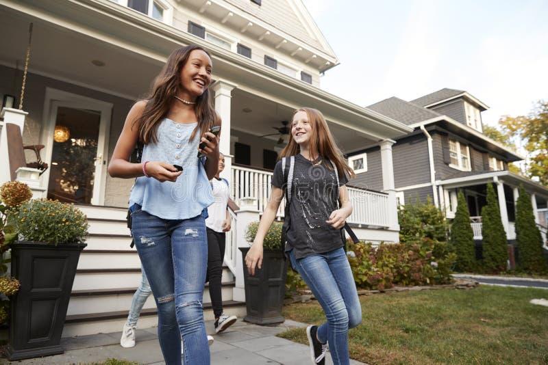 Amies de jeune adolescent quittant une maison pour l'école photos stock