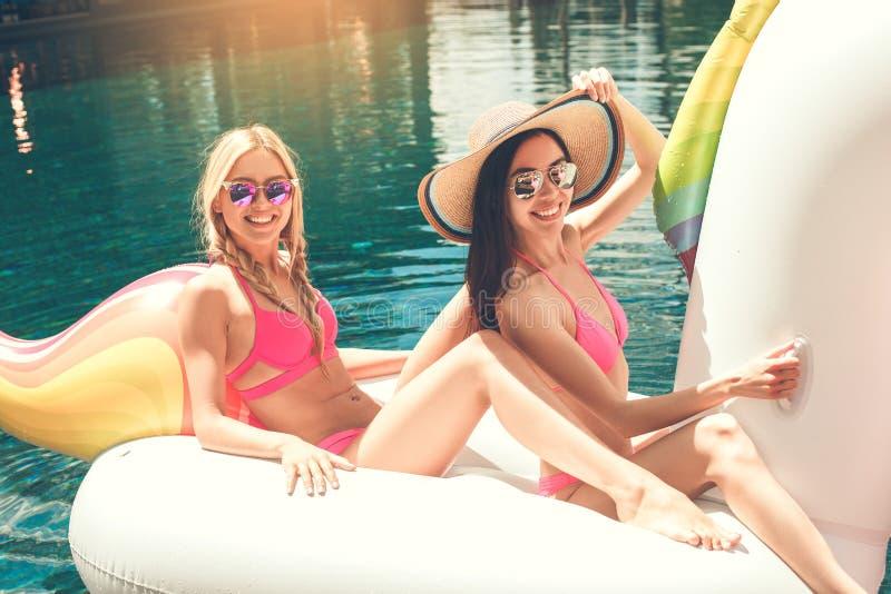 Amies de jeunes femmes dans l'amusement de piscine photographie stock libre de droits