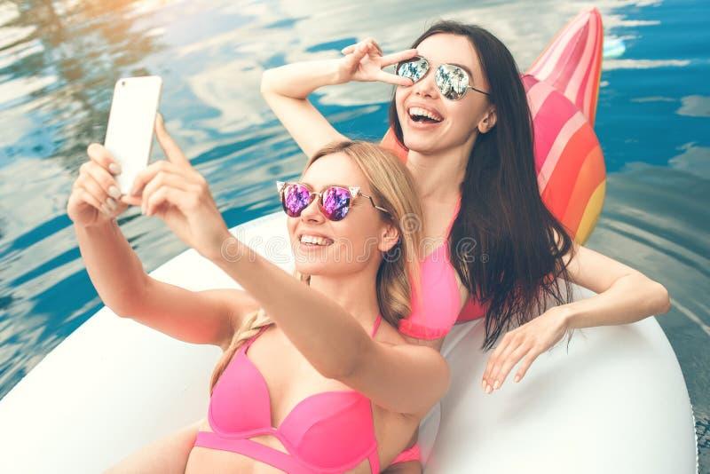 Amies de jeunes femmes dans l'amusement de piscine photo libre de droits