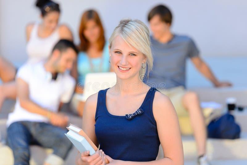 Amies de sourire de fille adolescente d'étudiant à l'arrière-plan image libre de droits