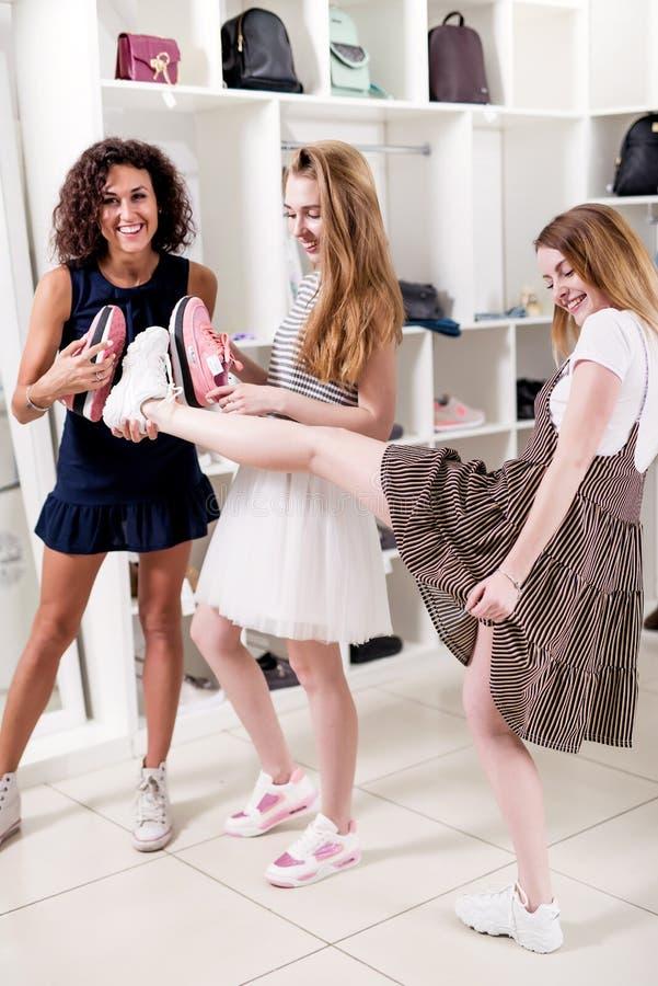 Amies de sourire drôles ayant l'amusement dans la boutique offrant de nouvelles chaussures à leur ami soulevant sa jambe pour vér image libre de droits
