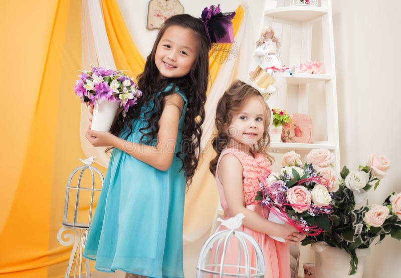 Amies mignonnes posant avec des bouquets des fleurs images stock