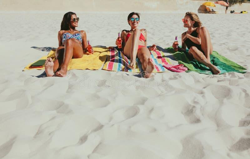 Amies prenant un bain de soleil sur la plage photographie stock
