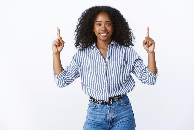 Amigável-olhando o penteado encaracolado energizado do estagiário afro-americano fêmea atrativo positivo que aumenta os indicador fotografia de stock