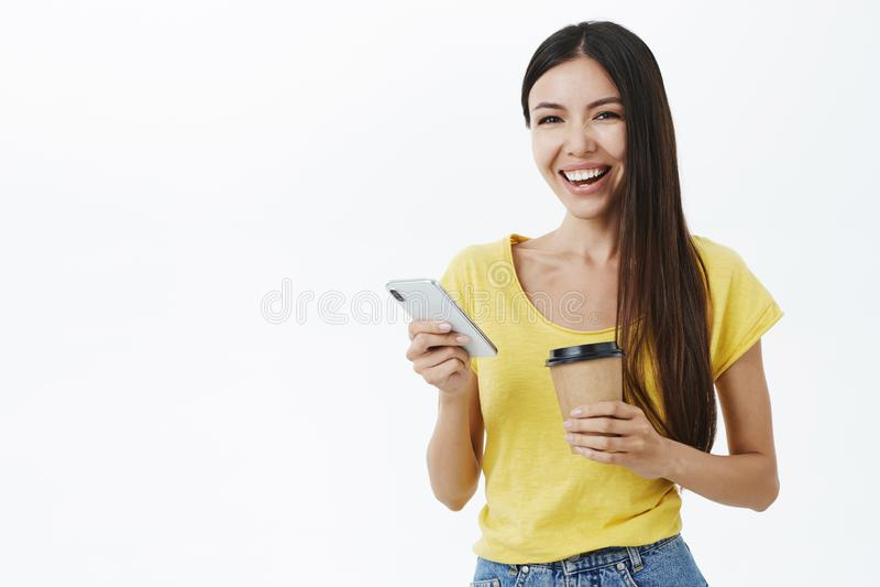 Amigável-vista mulher europeia atrativa alegre e mantida distraído com cabelo longo no t-shirt amarelo na moda que guarda o papel fotografia de stock