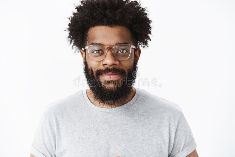Amig?vel-vista n?madas digital masculino farpado afro-americano que parte e agrad?vel nos vidros com sorriso afro do penteado imagem de stock