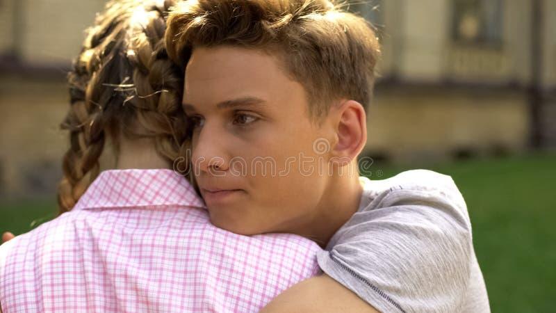 Amiga adolescente de abraço triste do homem novo, crise do relacionamento, dificuldades foto de stock royalty free