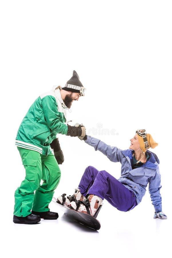 Amiga de ajuda do Snowboarder a levantar-se foto de stock royalty free