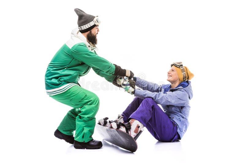 Amiga de ajuda do Snowboarder a levantar-se fotografia de stock royalty free