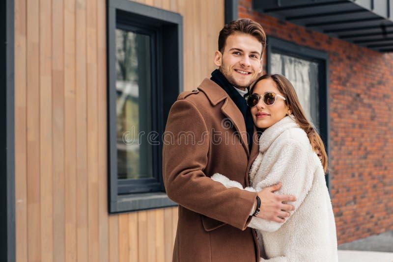 Amiga de amor que abraça seu homem forte ao andar a parte externa foto de stock royalty free