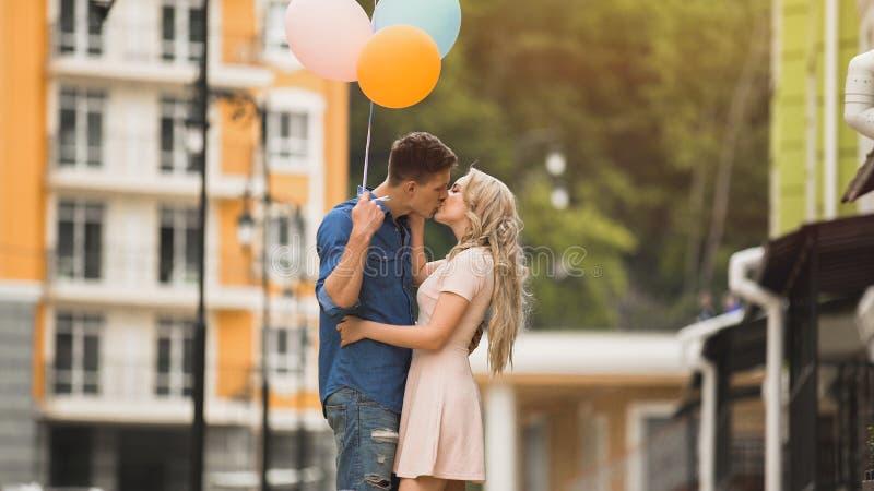 Amiga e noivo com balões que beijam na rua, relacionamento romântico imagem de stock