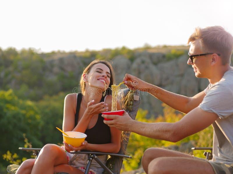 Amiga e noivo que comem macarronetes em um fundo natural Pares felizes do turista que têm o divertimento Conceito barato do turis fotografia de stock royalty free