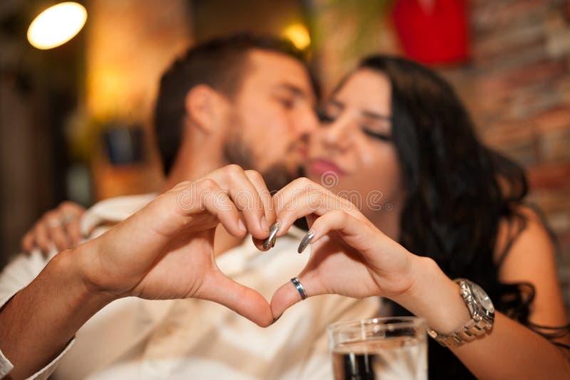 A amiga e o noivo que fazem o coração dão forma com suas mãos imagens de stock