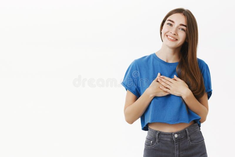 Amiga encantador macia com cabelo marrom no t-shirt azul que guarda as palmas no coração no gesto grato que inclina a cabeça imagem de stock