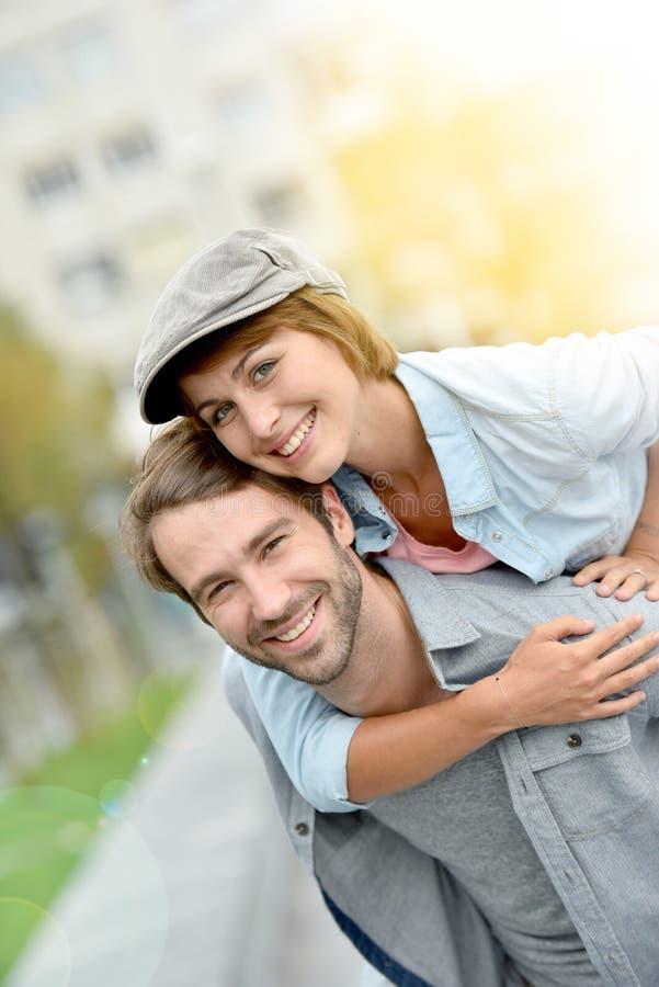 Amiga levando de sorriso do homem no seu para trás fotos de stock