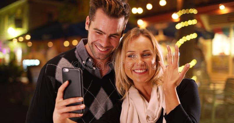 Amiga milenar que toma selfies com seu anel de noivado novo foto de stock