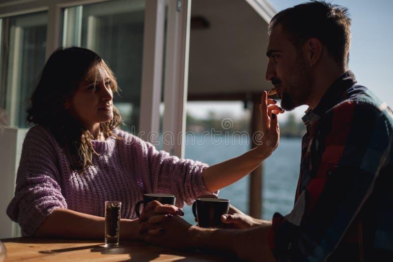 Amiga que alimenta seu noivo com uma cookie pelo rio imagens de stock
