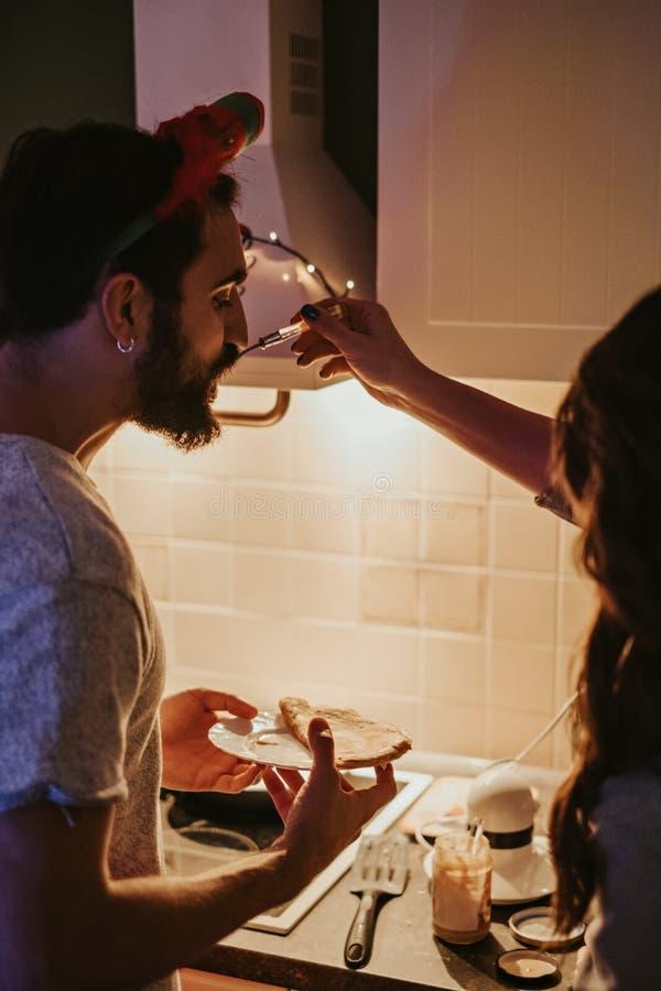 Amiga que alimenta seu noivo na cozinha fotografia de stock royalty free