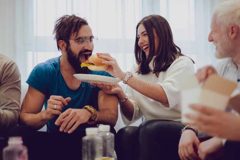 Amiga que alimenta seu noivo na frente dos amigos foto de stock