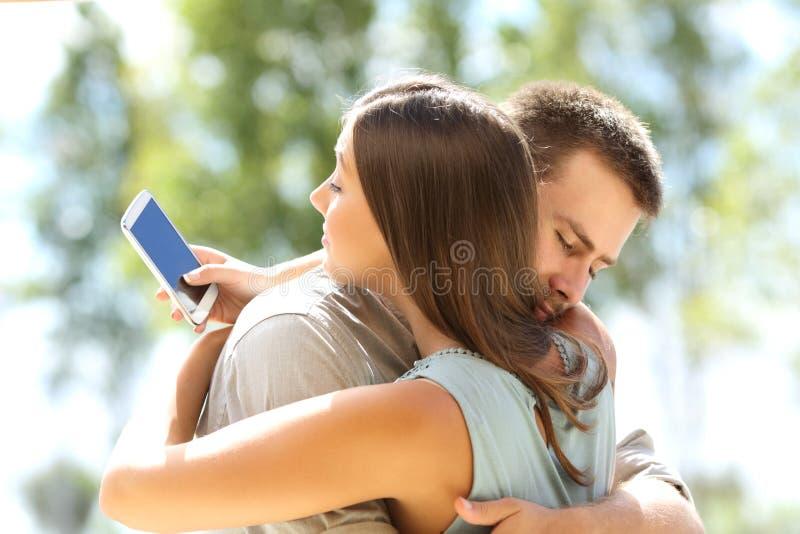 Amiga que engana e que abraça seu noivo imagens de stock