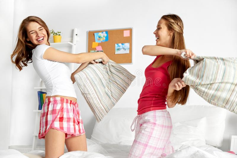 Amigas adolescentes felices que luchan las almohadas en casa imagenes de archivo